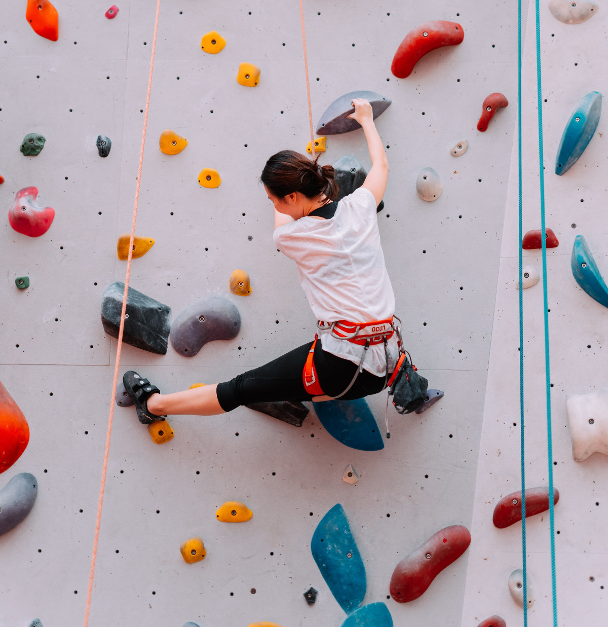 Woman climbing on an obstacle wall