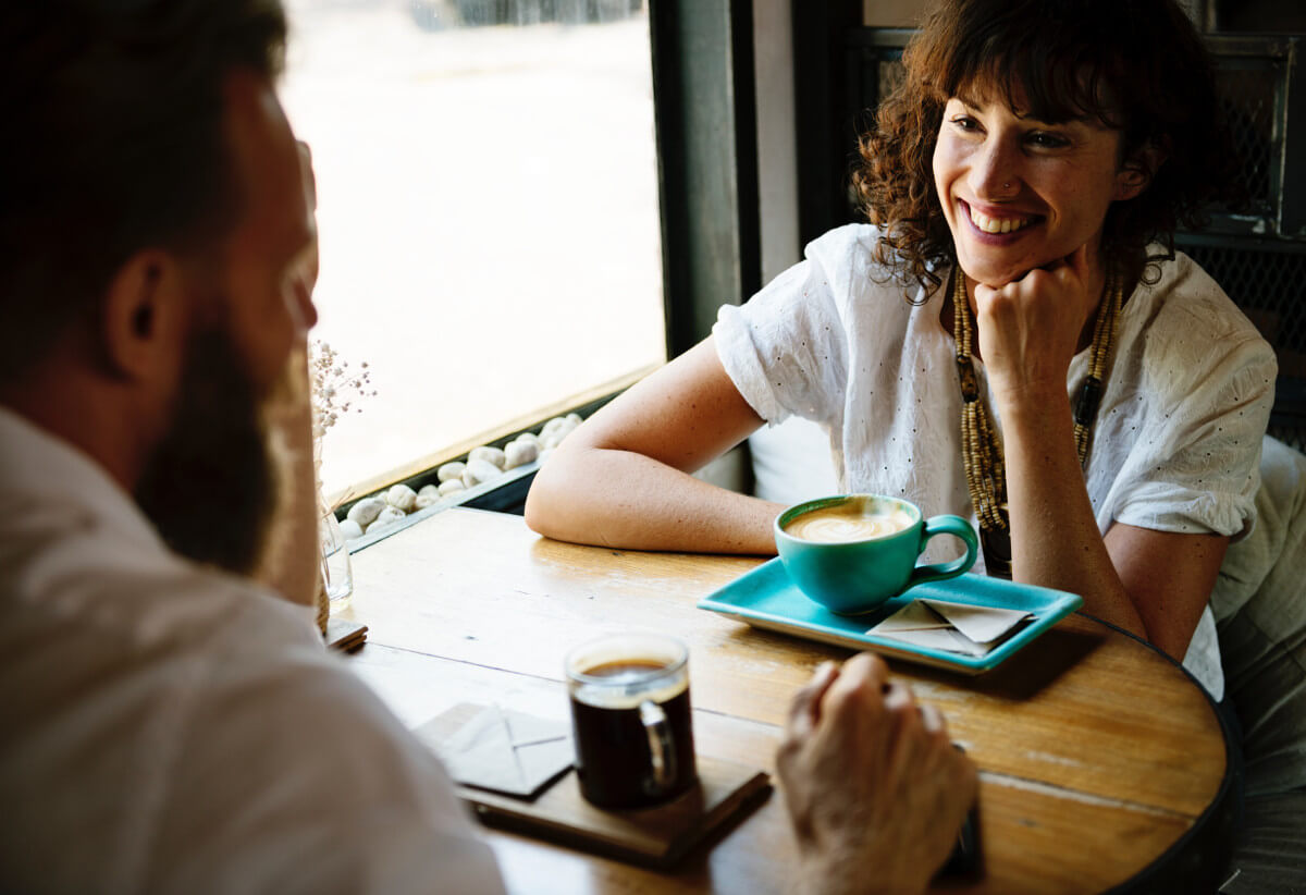 Man and woman smiling over coffee