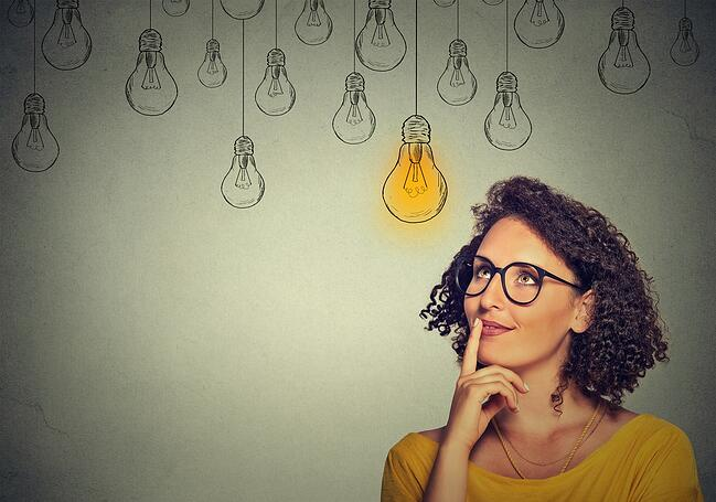 Woman in glasses thinking with lit idea bulb above her head