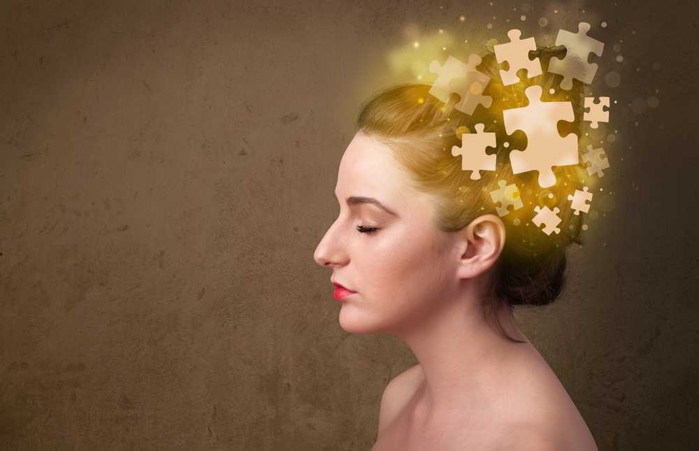 Young woman thinking with glowing puzzle pieces on mind